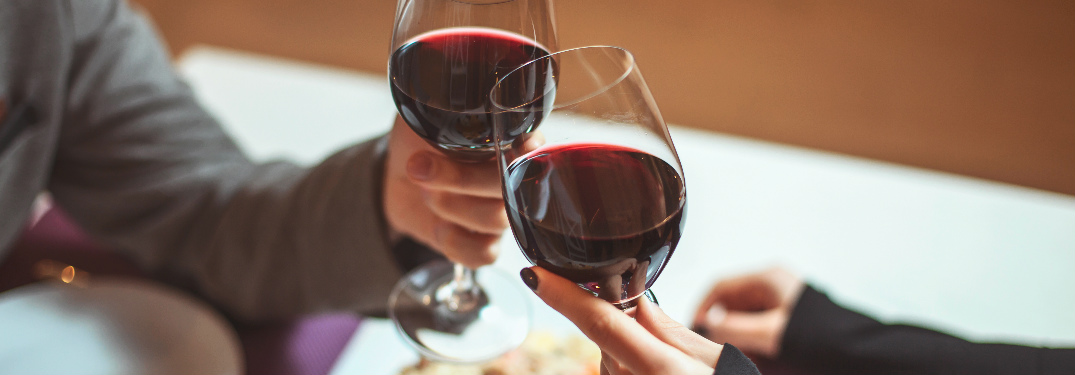 A couple clinking their wine glasses together over dinner