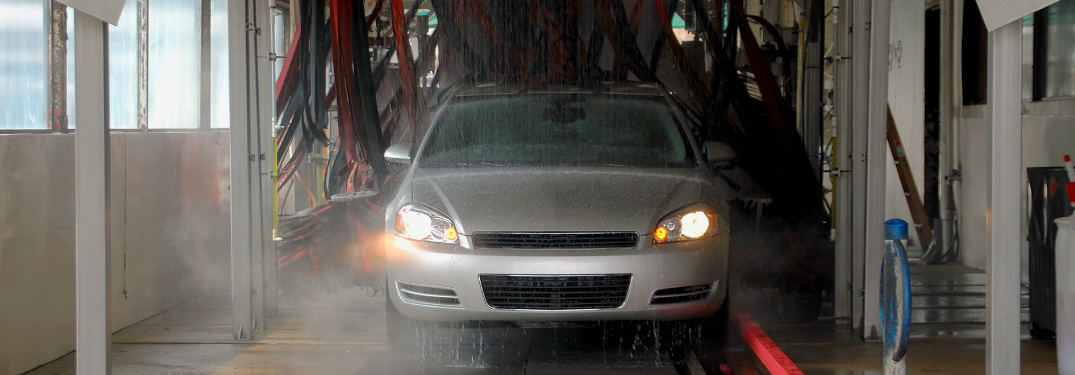 Grey sedan traveling through a car wash