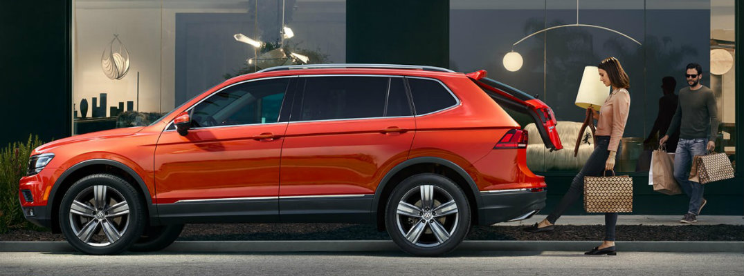 2018 Volkswagen Tiguan parked with lift gate open and woman loading shopping bags