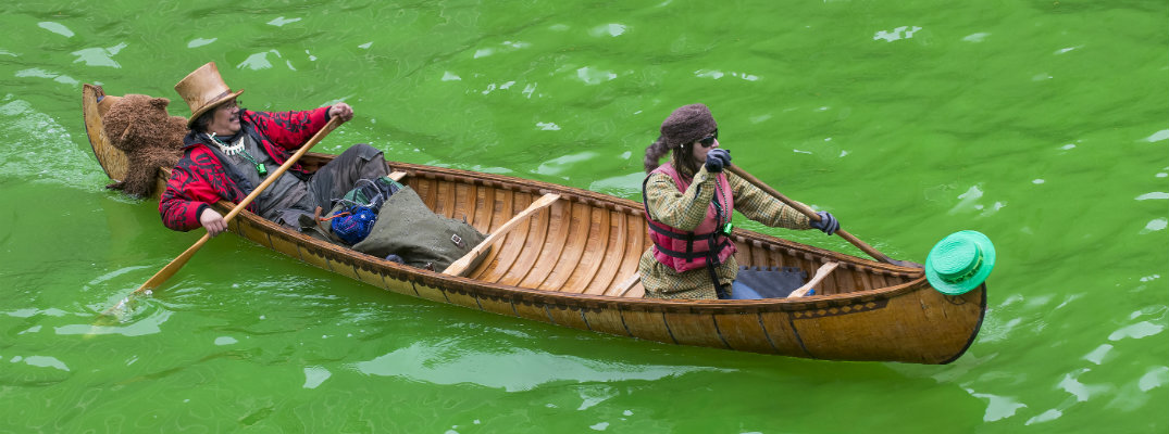 2 people canoeing in costumes down the green dyed Chicago River on St. Patrick's Day