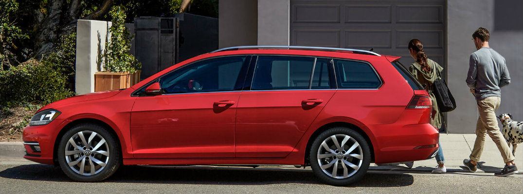2018 Volkswagen Golf SportWagen red exterior side shot parked in front of a house garage as a couple and their dog walk past it