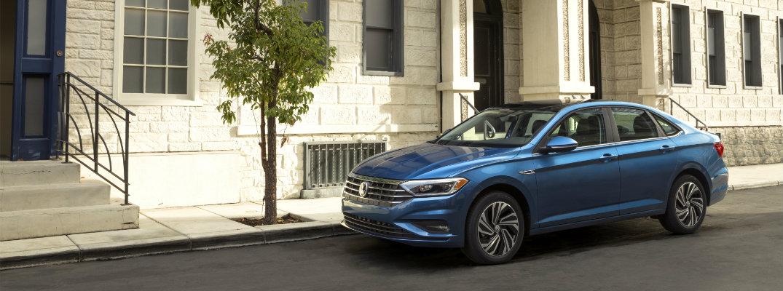 2019 Volkswagen Jetta blue exterior shot parked in a city neighborhood street