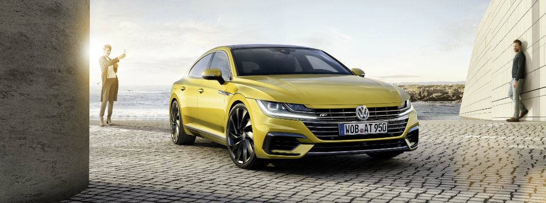 2019 Volkswagen Arteon exterior shot yellow paint job parked on tiles next to the sea as two men look at it in admiration