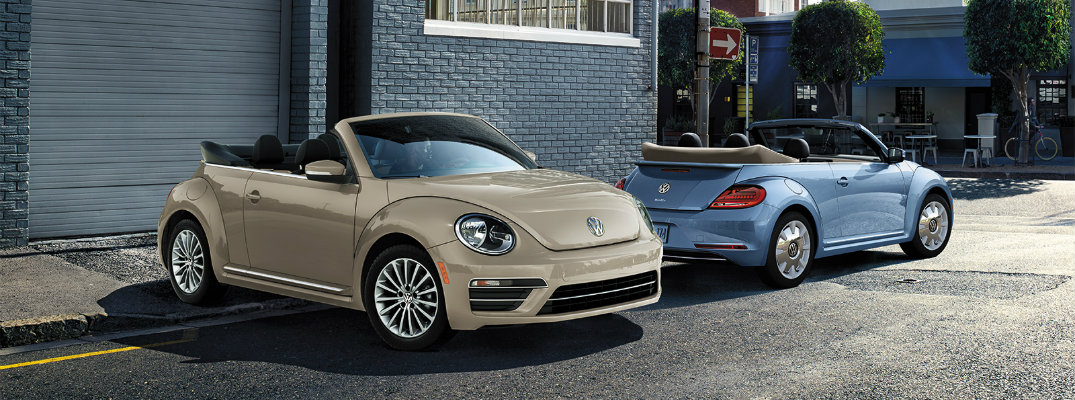 2019 Volkswagen Beetle Final Edition Convertible models Safari Uni and Stonewashed Blue colors parked outside a blue building