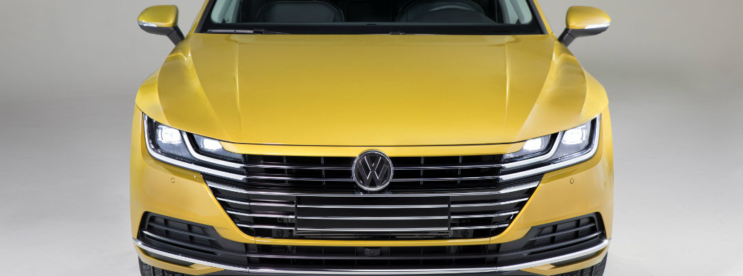 2019 Volkswagen Arteon front shot cropped of grille, vw badge, and LED headlights atop tumeric yellow paint color