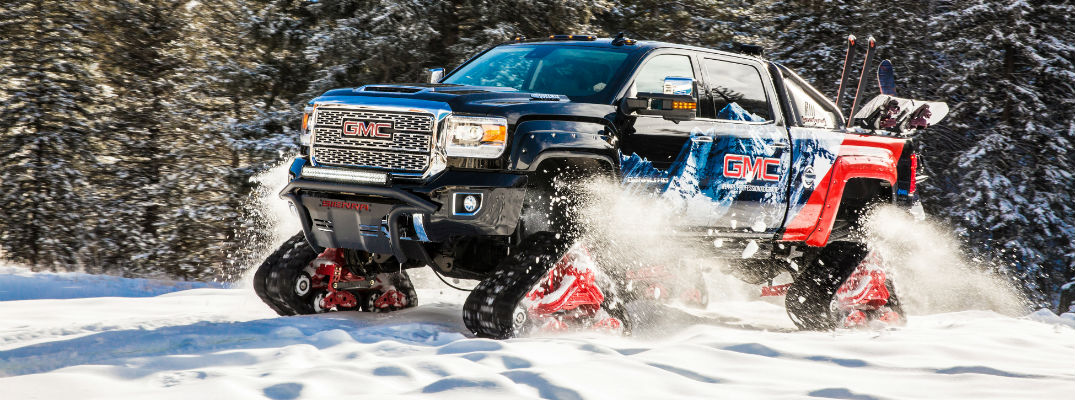 A profile view of the 2018 GMC Sierra 2500HD All Mountain concept truck running through the snow
