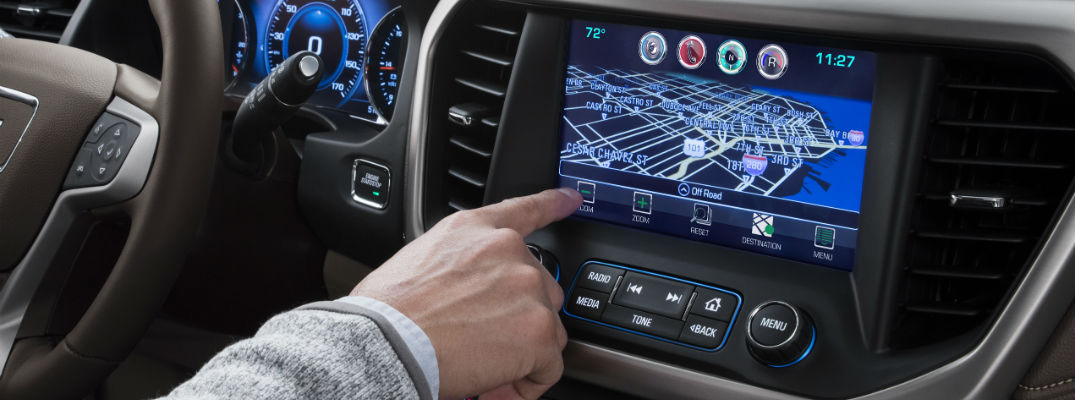 A close up photo of a driver using the GMC infotainment system.