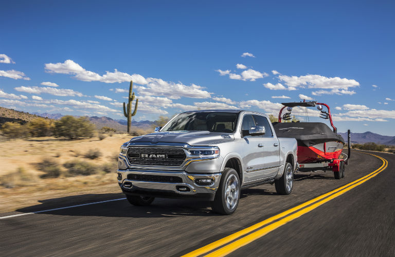 A photo of a 2019 Ram 1500 towing a boat on the highway