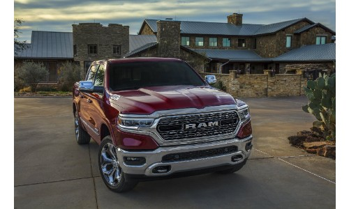 2019 Ram 1500 exterior shot parked outside fancy brick house with cloudy sky