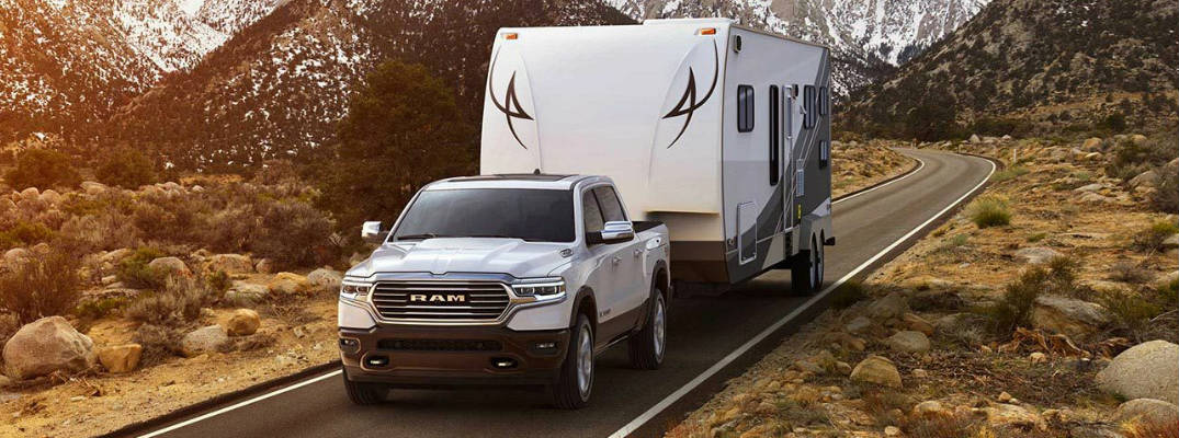 White 2019 Ram 1500 Towing a Trailer on a Country Road with Mountains in the Background