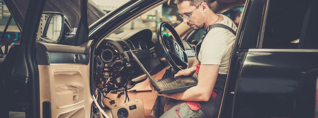 A stock photo of a technician working on a vehicle.