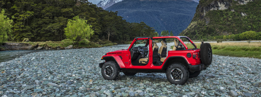A left profile photo of the 2018 Jeep Wrangler in a dry creek bed with the doors removed.