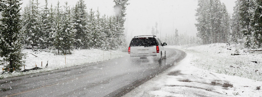 A stock photo of a GMC SUV driving on a possibly slippery road.
