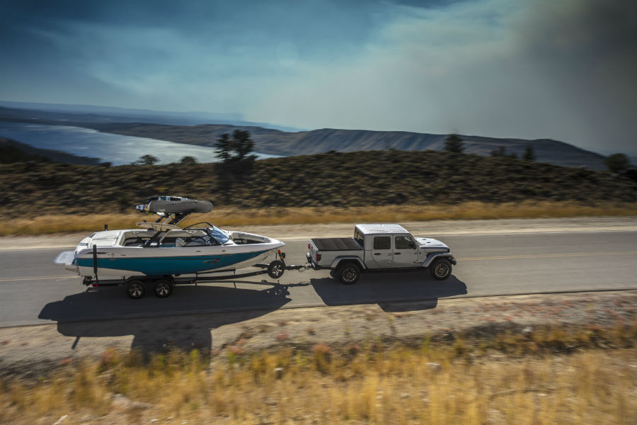 A photo of the 2020 Jeep Gladiator towing a boat on the road.