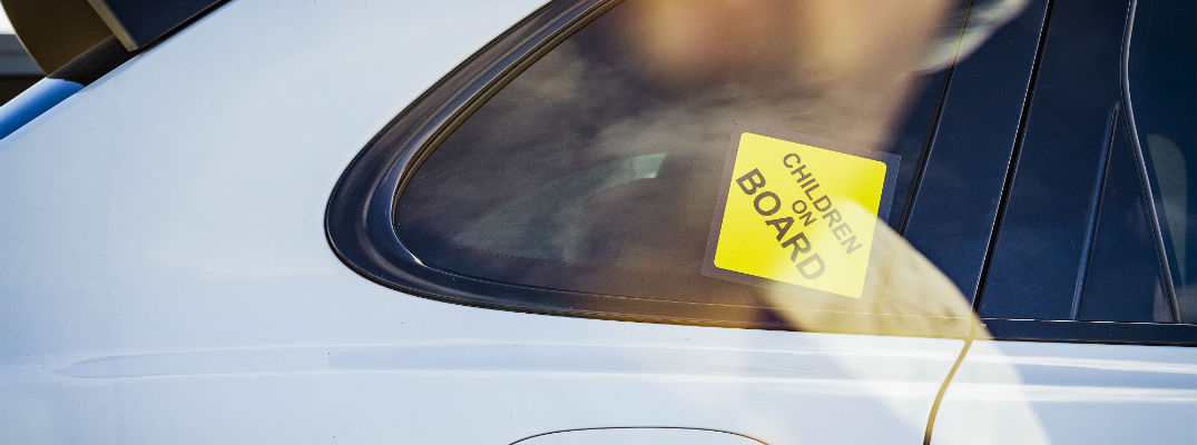 A stock photo of a Baby On Board sign in the window of a car.