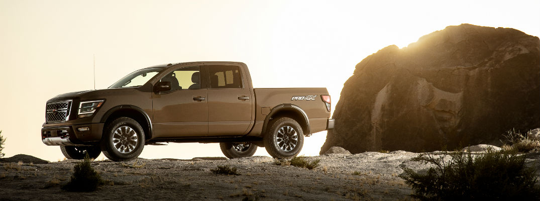 A left profile photo of the 2020 Nissan Titan parked near a rock.