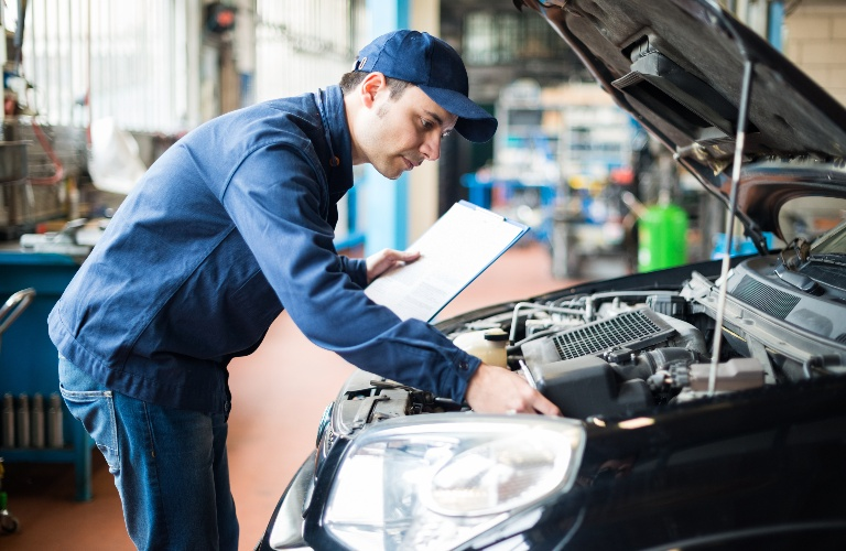 Mechanic working under the hood of a vehicle