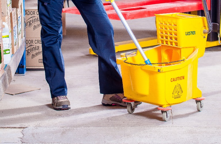 Person's legs and bucket with mop
