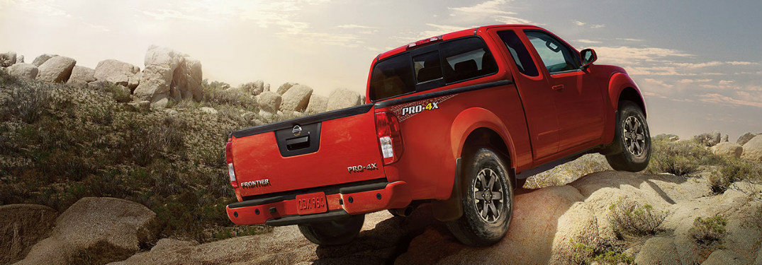 Red 2018 Nissan Frontier driving up hill off-road