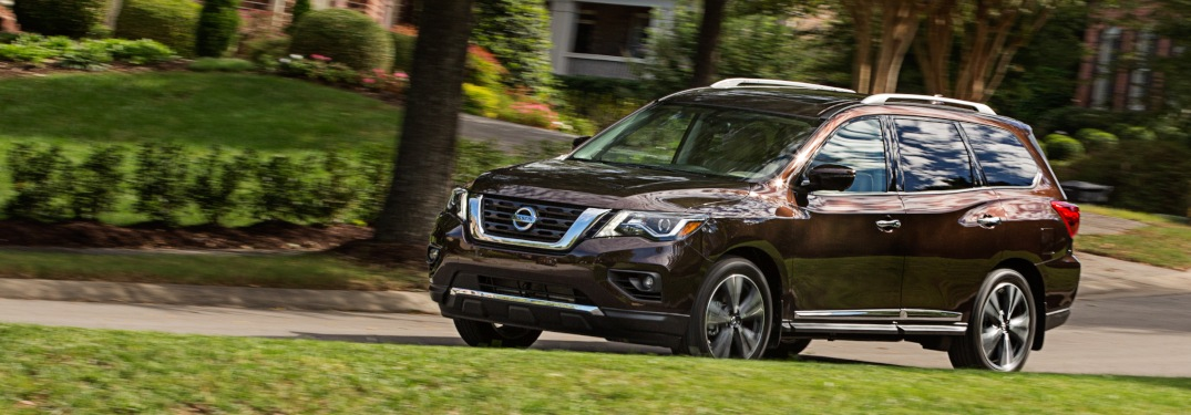Side view of a 2019 Nissan Pathfinder driving in residential area