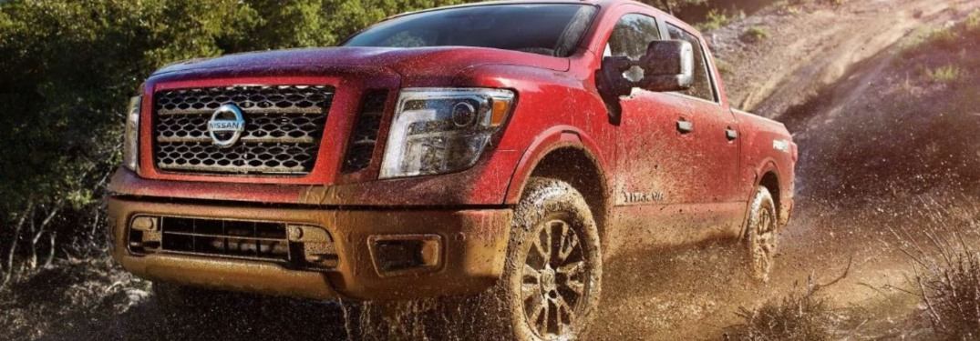 Red 2019 Nissan TITAN driving through mud
