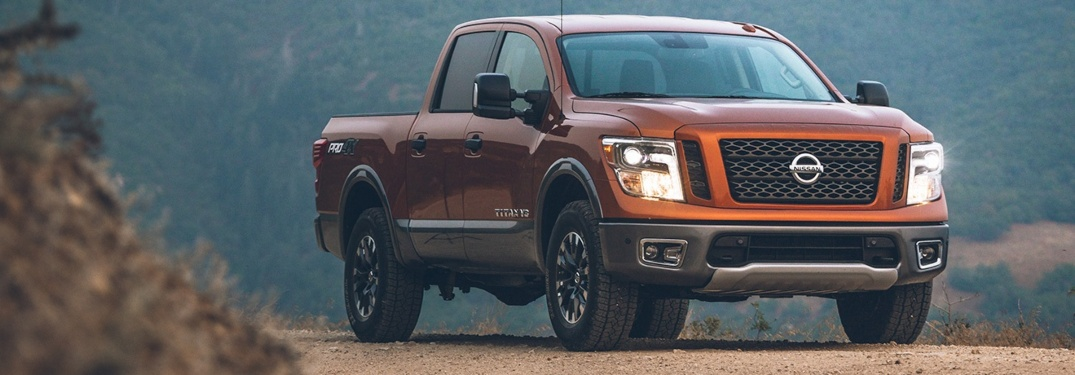 Front side view of a orange 2019 Nissan TITAN XD at dusk