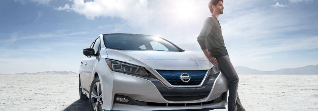Man leaning against a white 2019 Nissan LEAF