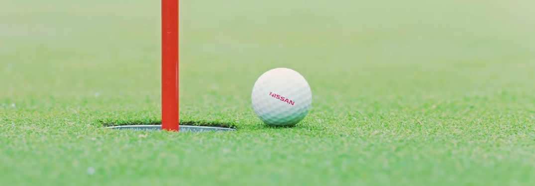 Nissan golf ball next to flagpin
