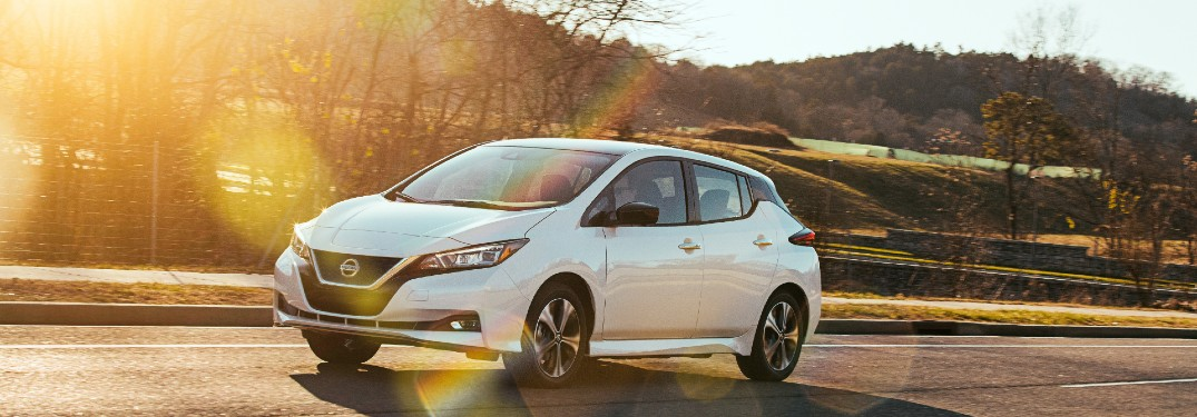 white Nissan Leaf driving down road