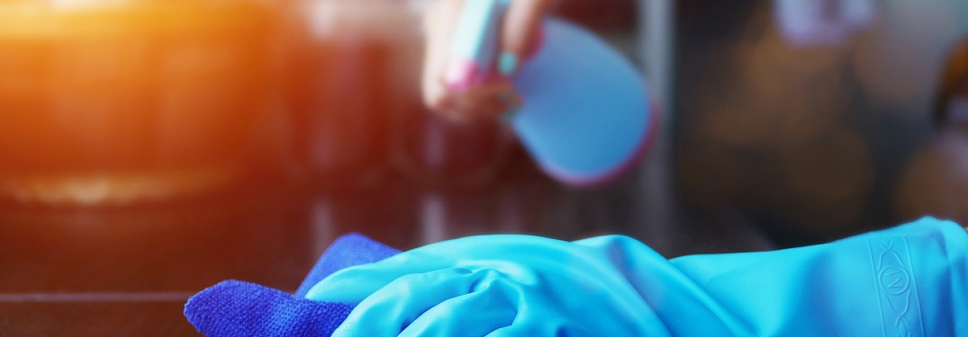 person cleaning with blue glove