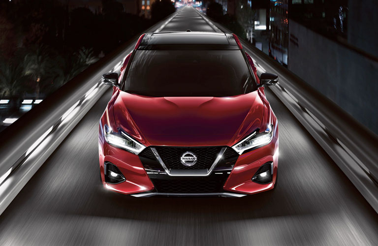 red 2020 Nissan Maxima driving on a bridge