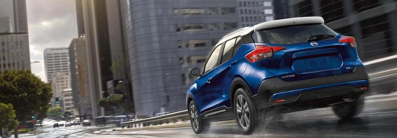 blue 2020 Nissan Kicks driving through the city