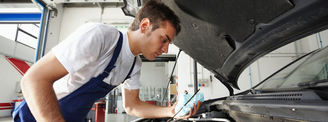mechanic working under hood of vehicle