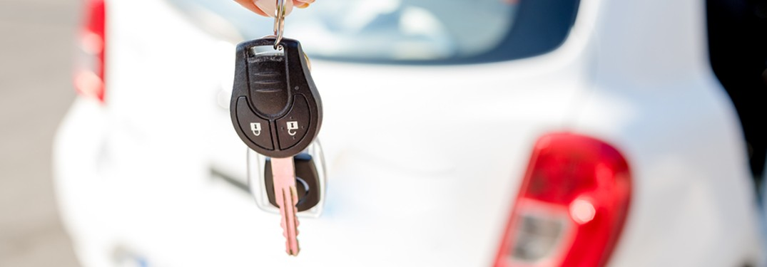 woman holding key behind car