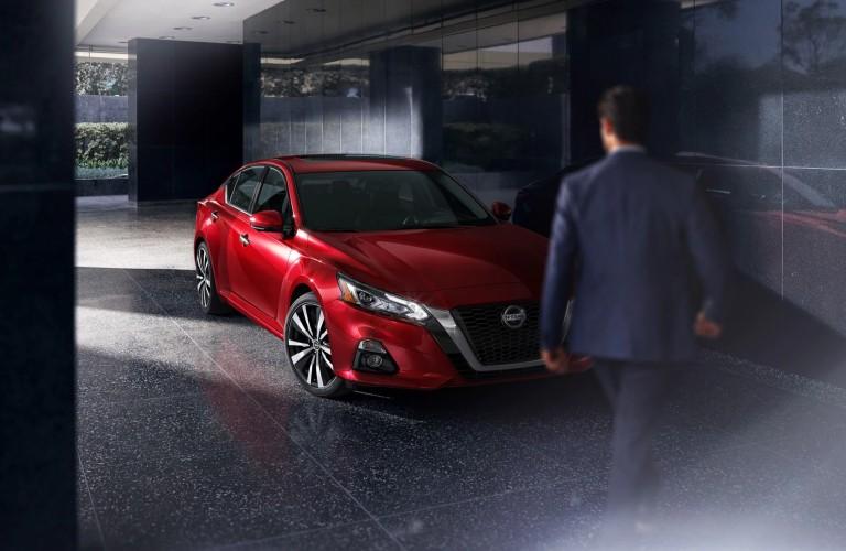 man walking toward red 2020 Nissan Altima