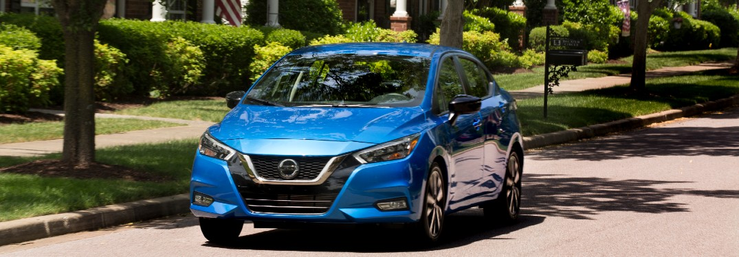 blue 2021 Nissan Versa driving through neighborhood