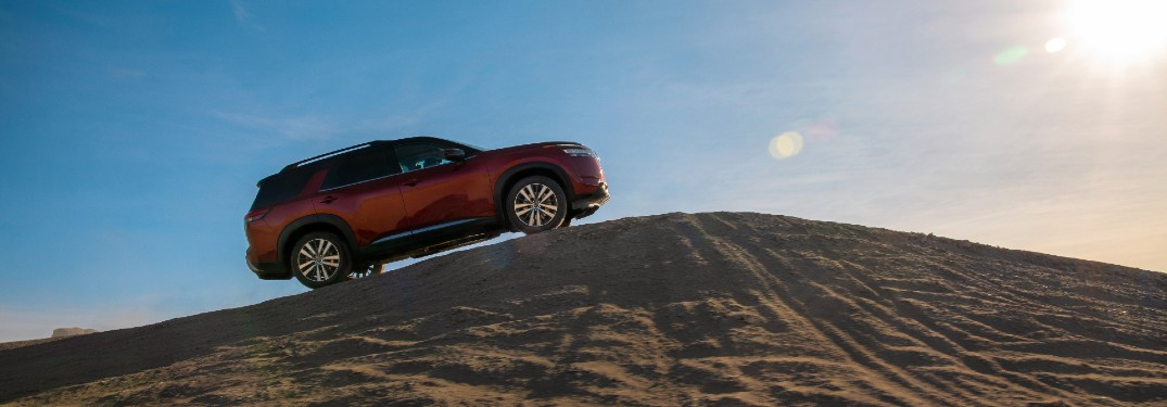 2022 Nissan Pathfinder driving up a sand hill