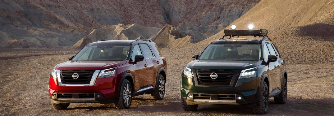 two 2022 Nissan Pathfinder models parked next to each other by a sand dune