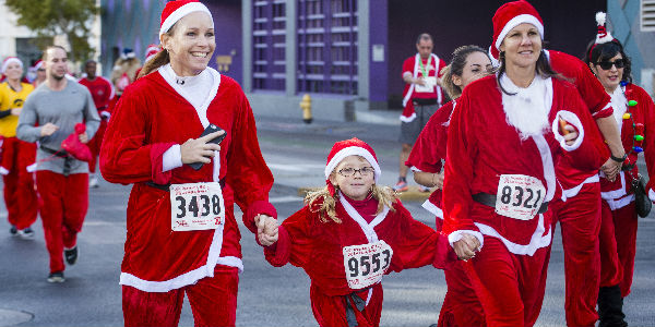Families Running a Race in Full Santa Suits on City Street