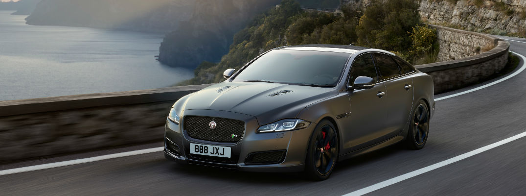 Gray 2018 Jaguar XJR 575 on Coast Road with Cliffs and Water in Background