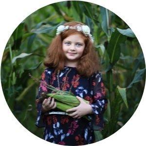 Little girl in a Cornfield Holding Corn