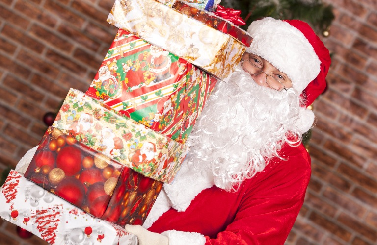 Santa Claus with large stack of presents