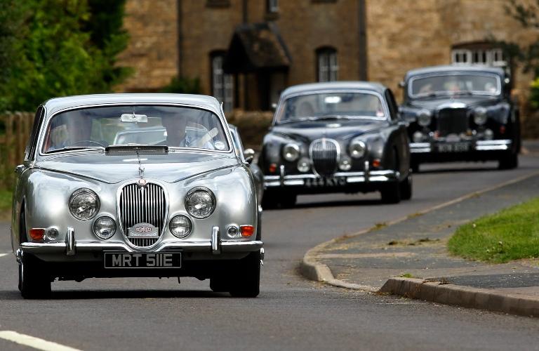 Three Jaguar MK II going down the street