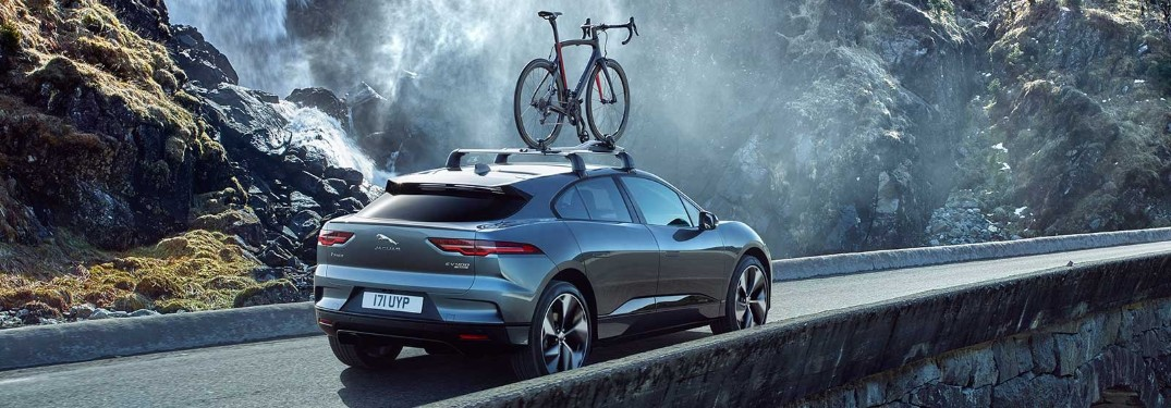 2020 Jaguar I-PACE going past a waterfall with a bike on top of it