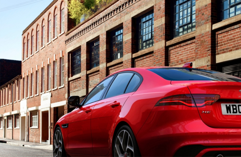 2020 Jaguar XE driving away with a large brick building in the background