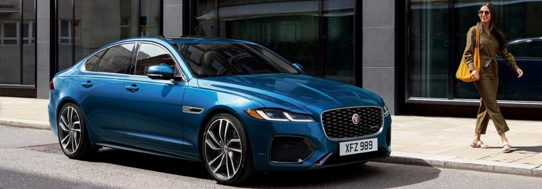2021 Jaguar XF on the side of the road and a woman walking on the sidewalk