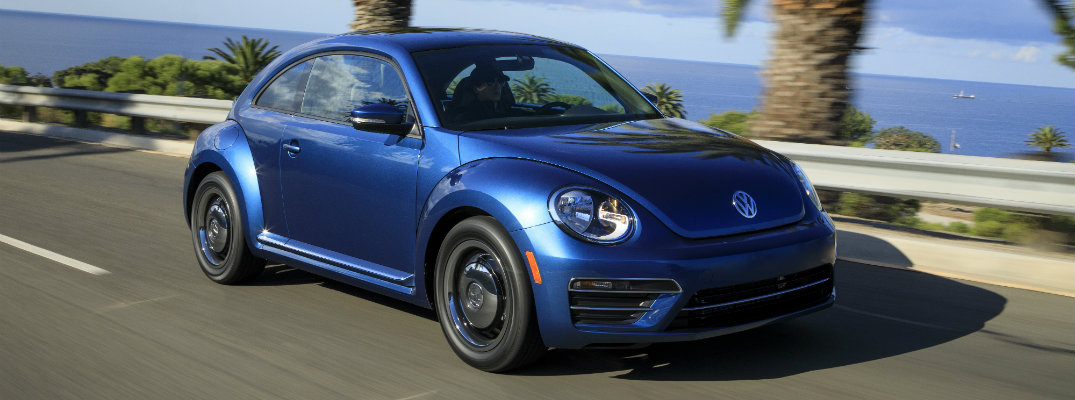2018 Volkswagen Beetle blue driving down road in tropical location by ocean and palm trees