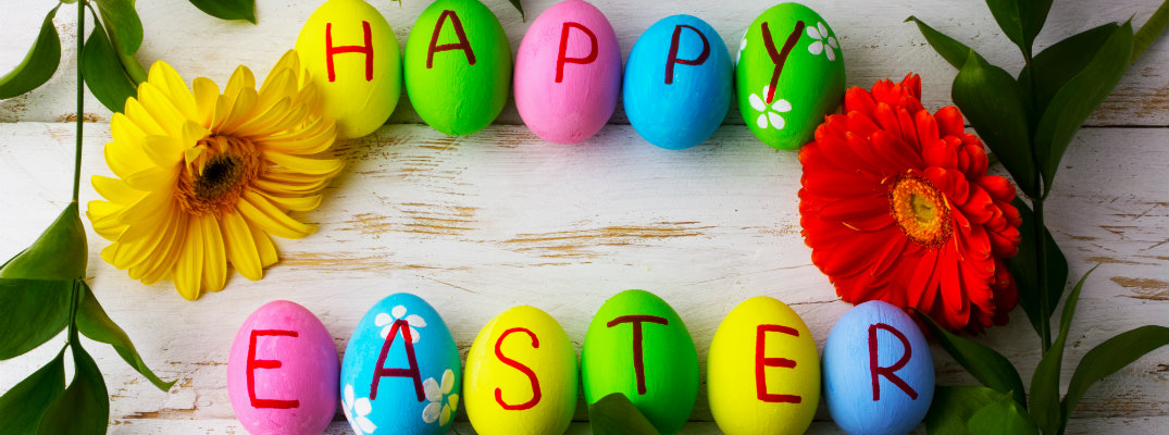 happy easter written on many color painted easter eggs on a wood nature carved table top counter