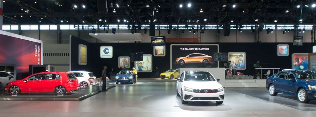 Volkswagen Auto Show display floor with screens, signs, and VW models such as the Golf, Passat, Jetta, and more