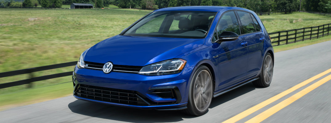 2018 Volkswagen Golf R exterior shot blue driving down a country highway next to a grassy field and wooden fence